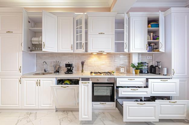 Interni di lusso in bianco moderno della cucina con ante e cassetti aperti