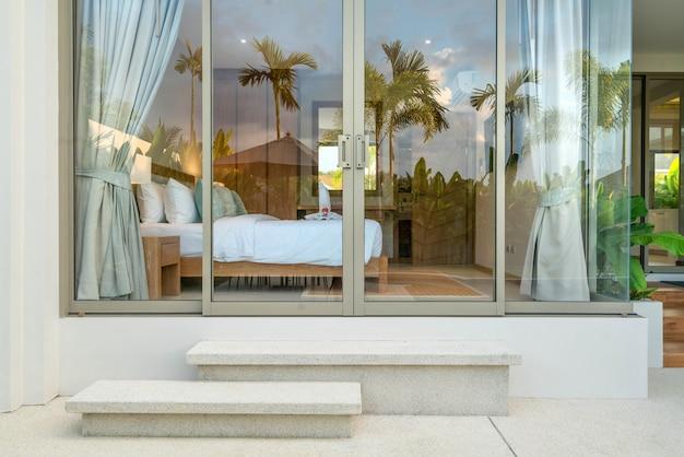 Interni di lusso nella camera da letto della villa con piscina con soffitto alto e rose sul letto della casa o dell'edificio