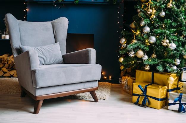 Interni di natale. parete blu con sedia. elegante albero di natale con doni in oro e argento.