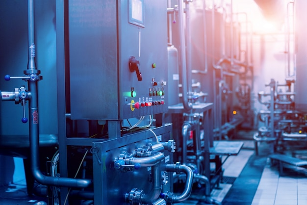 Interni moderni di un birrificio. botti e tubi. interni di fabbrica.