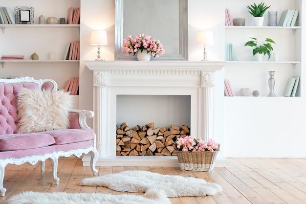 Interni moderni e luminosi con camino, fiori primaverili e accogliente divano rosa