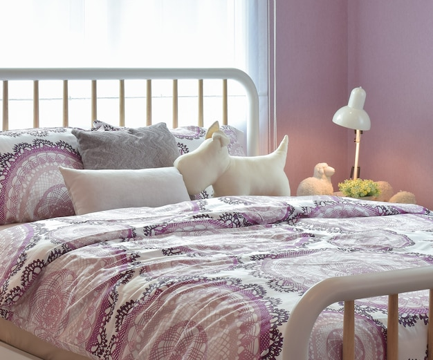 Interno accogliente della camera da letto con cuscini e lampada da lettura sul comodino