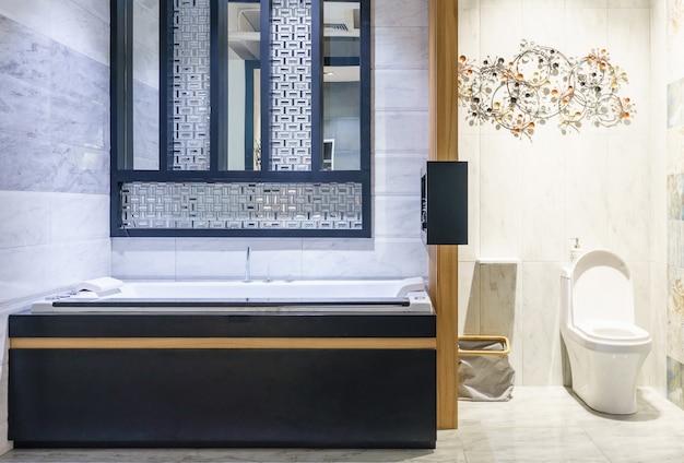 Interno bagno moderno con doccia minimalista e illuminazione, wc bianco, lavabo e vasca