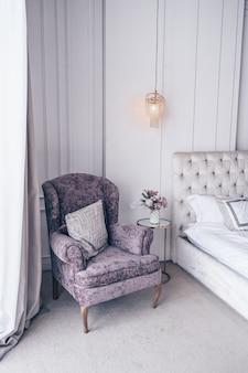 Interno camera da letto classica bianca con bouquet per le vacanze di capodanno in un vaso, una confezione regalo delicatamente rosa sul comodino in vetro e una poltrona classica nei colori lavanda