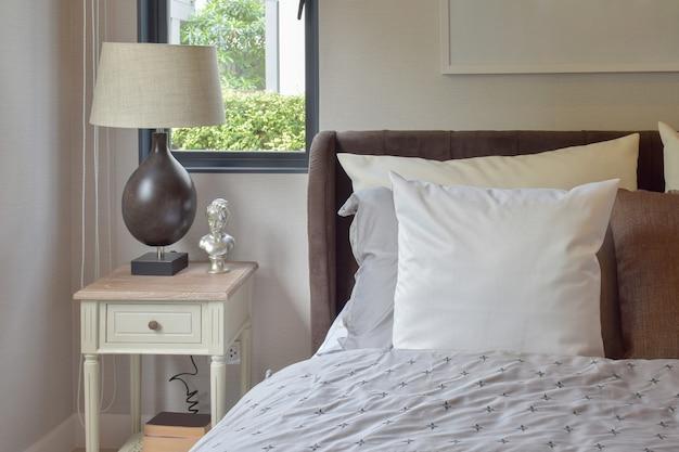 Interno camera da letto moderna con cuscino bianco e marrone sul letto e lampada da tavolo decorativa