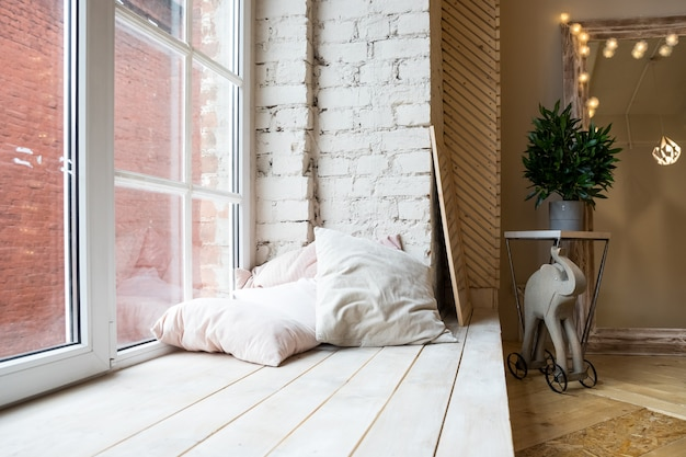 Interno con grande finestra, pavimento in legno. design della camera da letto in stile loft.