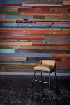 Interno con pavimento in legno colorato multi parete in legno scuro e sedia vintage minuscola