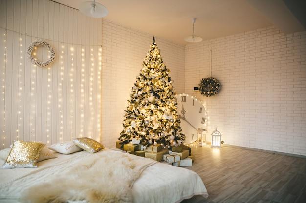 Interno decorato per natale a tema con abete e molti accessori per natale. stile di decorazione dorata bianca