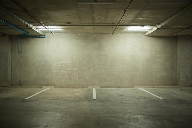 Interno del grande magazzino del garage di parcheggio con il tabellone per le affissioni in bianco
