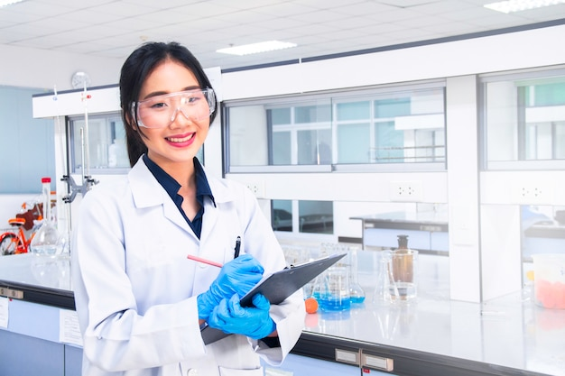 Interno del laboratorio pulito o moderno di chimica o medico. scienziato di laboratorio che lavora in un laboratorio. concetto di laboratorio con chimico donna asiatica.