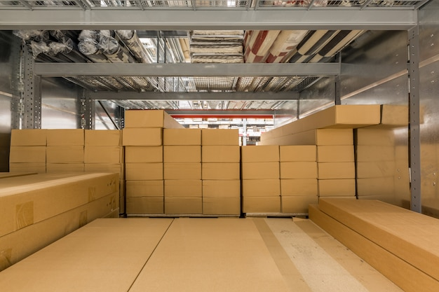 Interno del magazzino con scaffalature per conservare materiale di produzione, pallet e scatole.