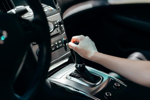 Interno del salone dell'automobile nera. mano femminile sulla trasmissione