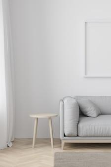 Interno del salotto in stile moderno con divano in tessuto, tavolino e cornice bianca vuota sul pavimento in legno