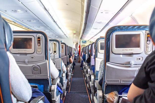 Interno dell'aeroplano con i passeggeri sui sedili durante il volo