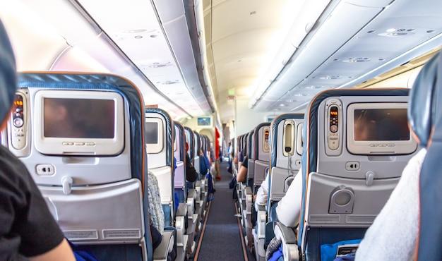 Interno dell'aeroplano con i passeggeri sui sedili in attesa di decollare