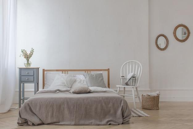 Interno della camera da letto accogliente bianca e grigia