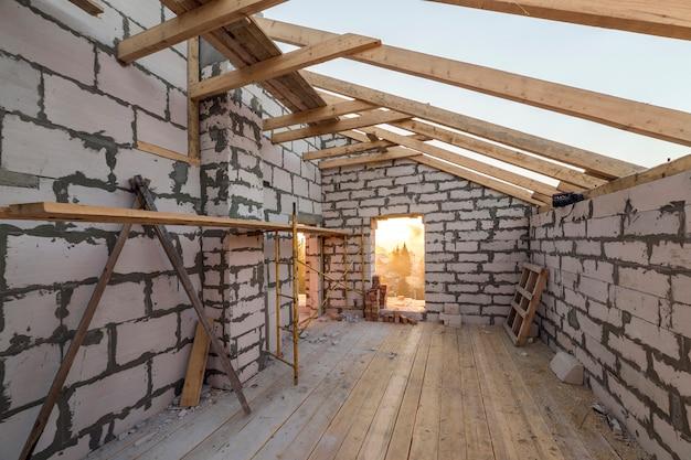 Interno della casa in costruzione e ristrutturazione. pareti a risparmio energetico di blocchi e mattoni isolanti in schiuma vuota, travi del soffitto e telaio del tetto.