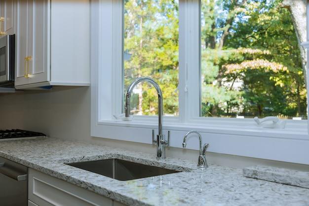 Interno della cucina moderna con elettrodomestici sul piano cottura, bancone in marmo con armadi bianchi da cucina