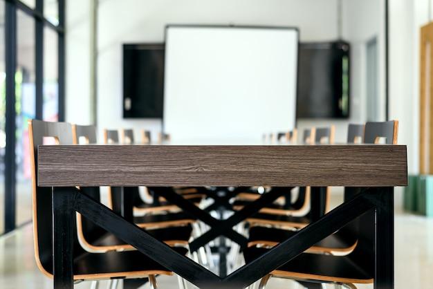 Interno della sala riunioni con la tavola e le sedie di legno in ufficio moderno