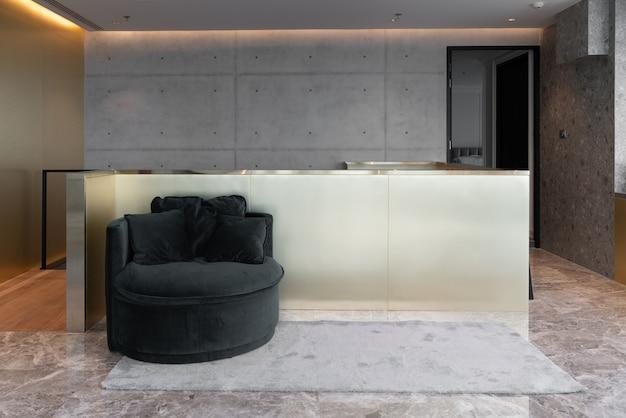 Interno di casa con divano circolare verde sul tappeto grigio e parete in acciaio inossidabile oro
