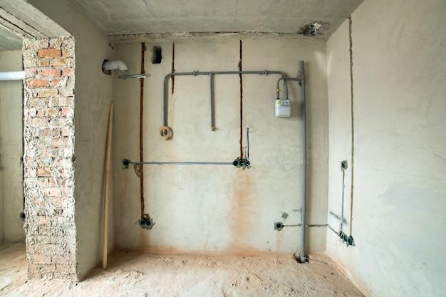 Interno di un appartamento con pareti nude e soffitto in costruzione.