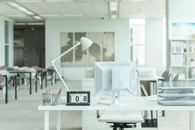 Interno di un ufficio moderno con computer e mobili bianchi