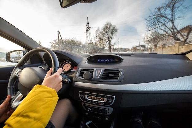 Interno moderno dell'automobile con le mani femminili dell'autista sul volante, paesaggio nevoso di inverno fuori. concetto di guida sicura.