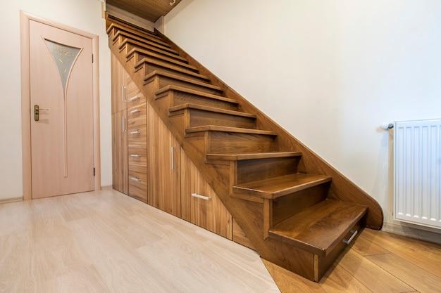 Interno moderno di architettura con il corridoio di lusso con le scale di legno lucide in casa moderna del piano. armadi estraibili personalizzati su scivoli nelle fessure sotto le scale