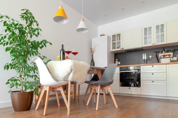 Interno moderno di cucina, muro bianco, sedie in legno, fiore verde in vaso. concept design scandinavo