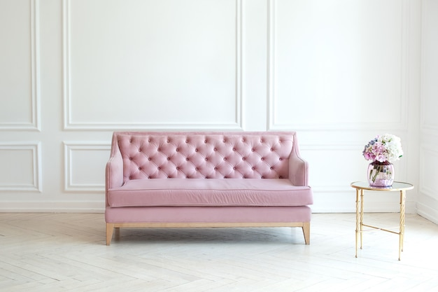 Interno moderno e minimalista del salone con un sofà rosa e una tavola con un vaso del mazzo dei fiori contro la parete bianca. l'ampio soggiorno in stile classico ha un divano in velluto. concetto di intimità