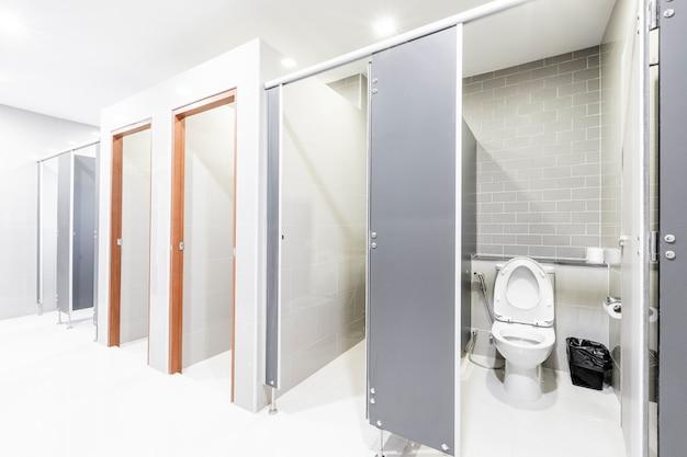 Interno pubblico del bagno con il bagno moderno allineato moderno.