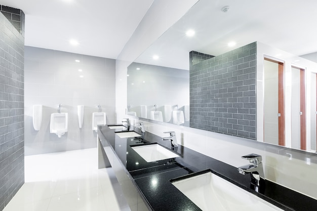 Interno pubblico del bagno con rubinetto del lavandino allineato moderno.
