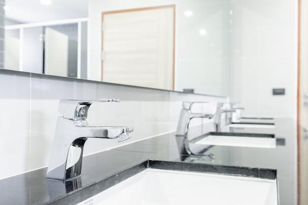 Interno pubblico del bagno con rubinetto lavabo lavabo rivestito