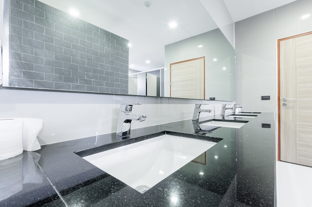Interno pubblico del bagno con rubinetto lavabo