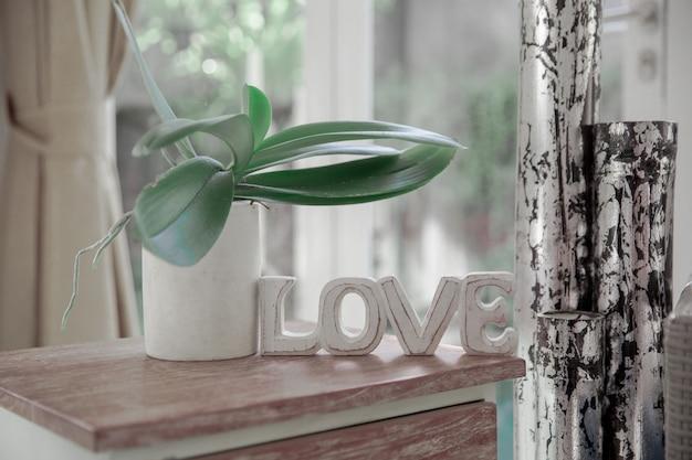 Interno scandinavo minimalista con divano di design, piante tropicali, tavolino, segno di amore