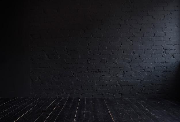Interno scuro con muro di mattoni nero e pavimento in legno nero