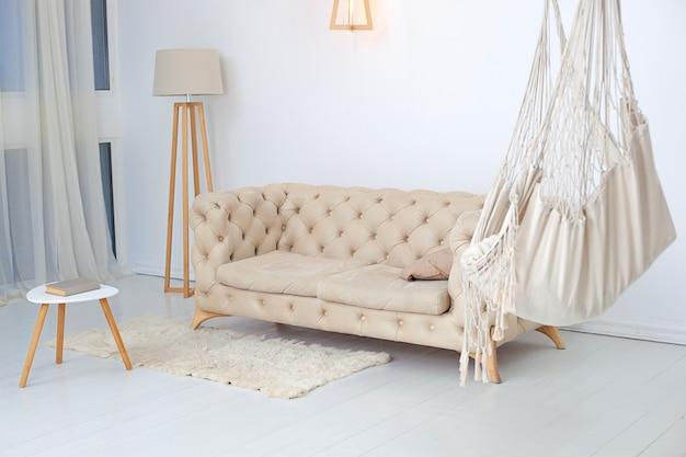 Interno soggiorno con amaca, soffice tappeto e tavolino con lampada. amaca moderna nell'interno del salone. loft multifunzionale con amaca accogliente, divano beige e grande finestra.