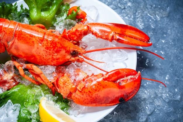 Intero aragosta rossa con pomodoro e fette di limone sul piatto bianco
