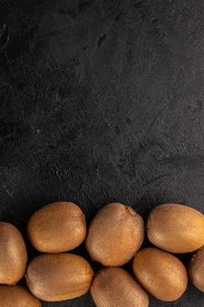 Intero morbido maturo di kiwi freschi isolato su un pavimento grigio