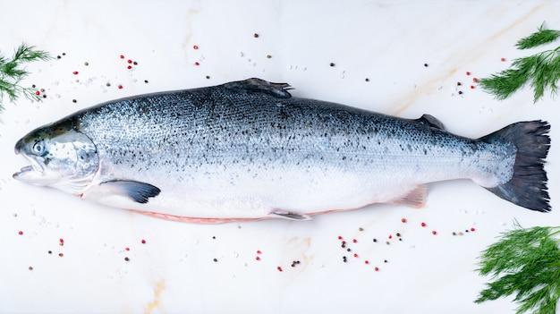 Intero pesce salmone grande crudo fresco con condimento, sale, pepe, aneto sul tavolo di marmo bianco, vista dall'alto