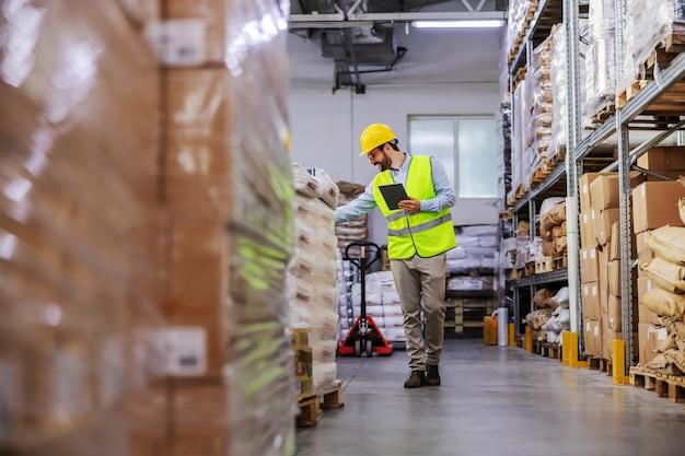Intero supervisore barbuto attraente che cammina intorno al magazzino e utilizza il tablet per controllare le merci per la spedizione.