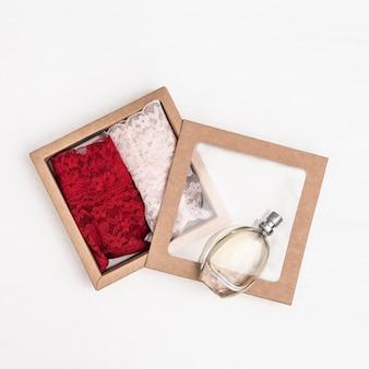 Intimo femminile alla moda per sorpresa romantica, mutandine da donna rosse e rosa in confezione regalo, bottiglia di vetro con profumo.
