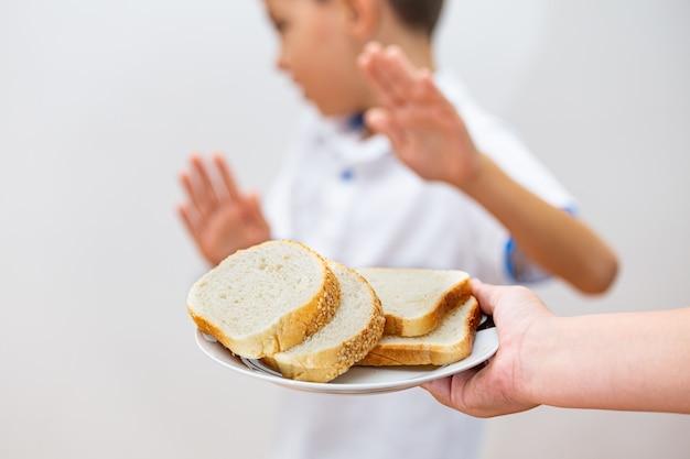 Intolleranza al glutine e concetto di dieta. il bambino rifiuta di mangiare il pane bianco.