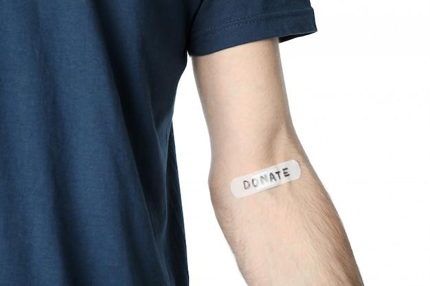 Intonaco adesivo con iscrizione dona sulla mano maschile isolata su uno spazio bianco