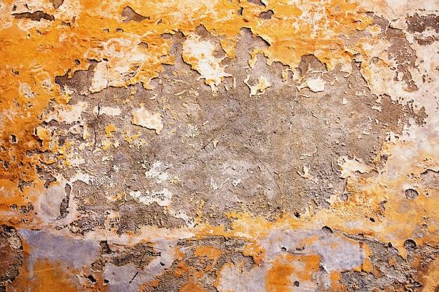 Intonaco distrutto giallo, arancione, grigio a un muro di mattoni. grunge cemento, con uno sfondo di vernice squallida.