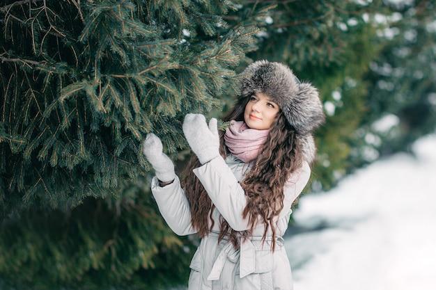Inverno della ragazza beaty del cappello di pelliccia vicino all'abete rosso