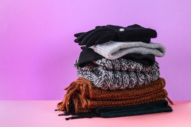 Inverno e autunno vestiti, cappelli, sciarpe, guanti su uno sfondo pastello viola.