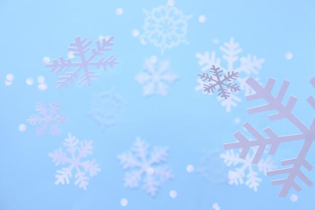 Inverno fiocchi di neve bianchi tagliati da carta bianca su sfondo blu.