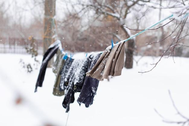Inverno. i vestiti si stanno asciugando per strada. i vestiti coperti di neve si asciugano su una corda tesa.