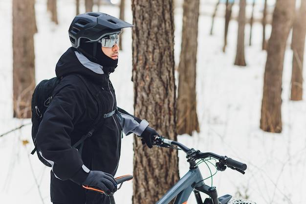 Inverno in sella a una mountain bike nella foresta.